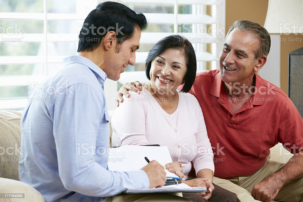 A financial advisor talking to an elderly couple in home stock photo