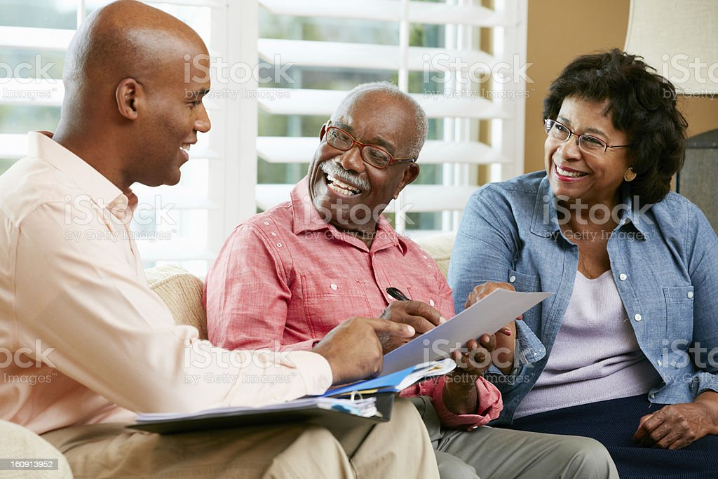 Financial Advisor Talking To Senior Couple At Home stock photo