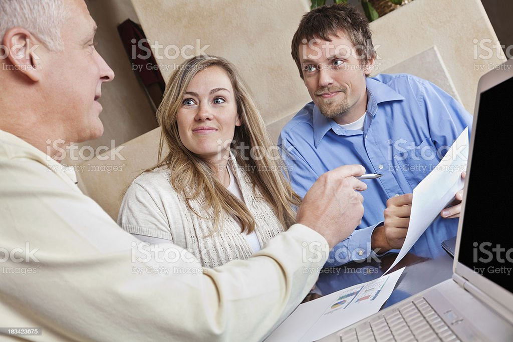 Financial Advisor Talking to Young Couple in Their Home royalty-free stock photo