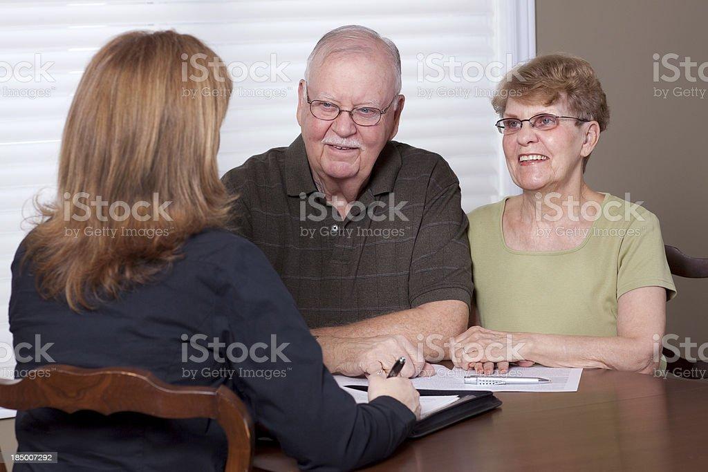 Financial advisor with seniors (table) stock photo