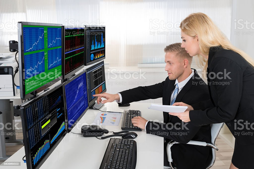 Financial Agents Monitoring Computer Screens In Office stock photo