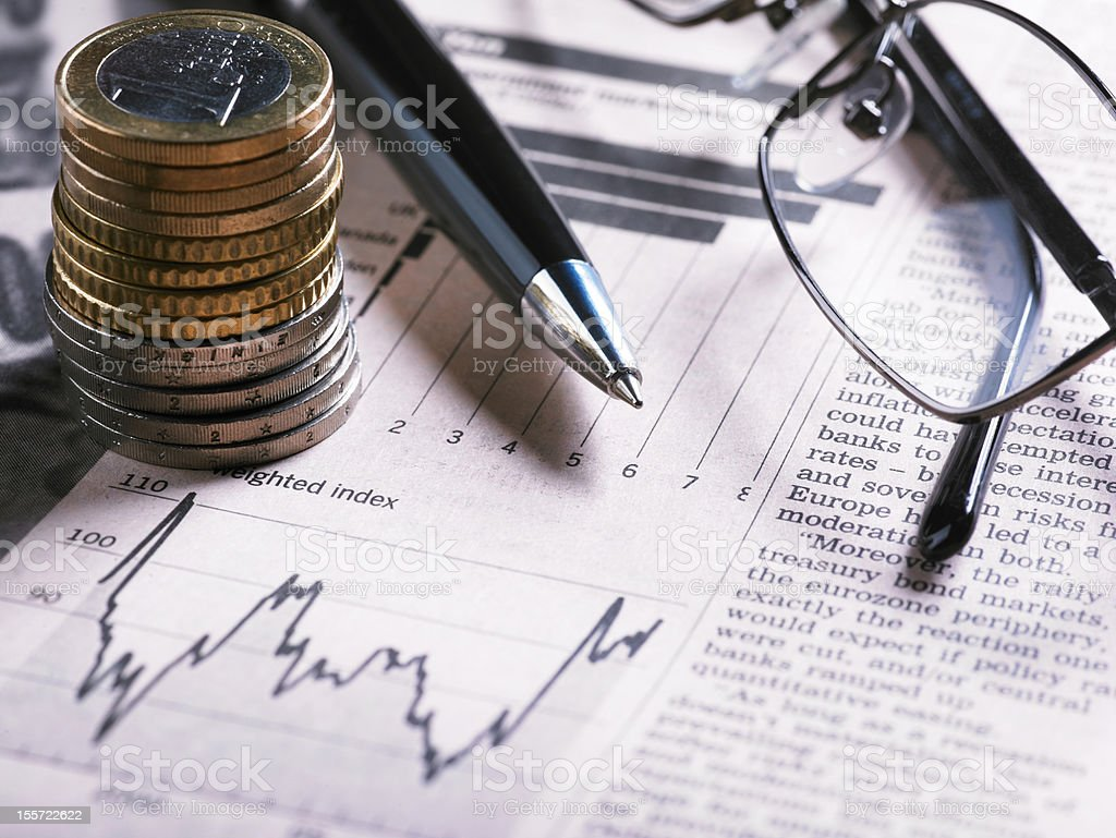 A financial chart with coins, glasses and pen stock photo