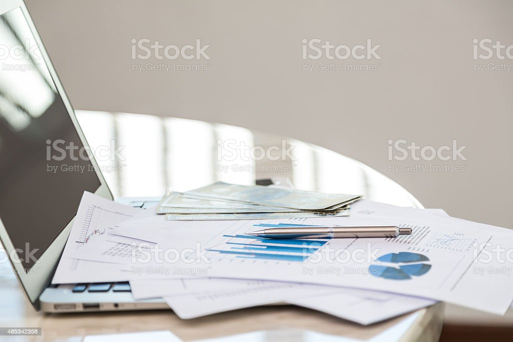 Financial charts on the table with laptop stock photo