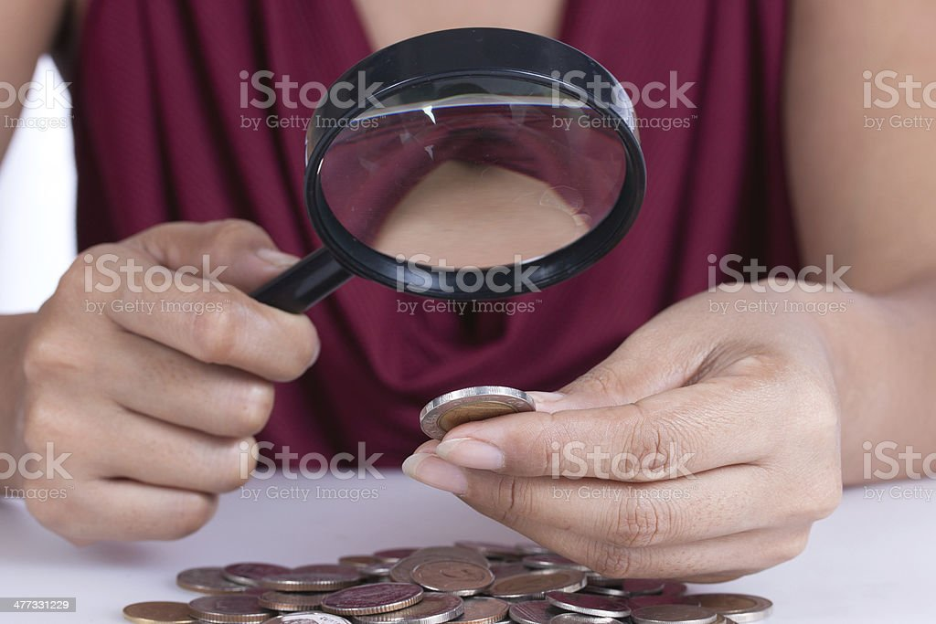 Financial concept, hand hold magnifying glass and coins royalty-free stock photo