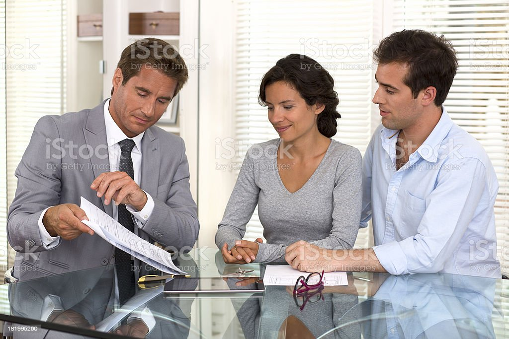 Financial consultant presents bank investments to a young couple royalty-free stock photo