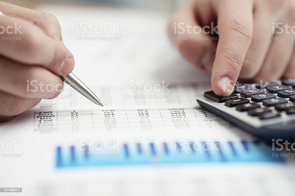 Financial data analyzing. Counting on calculator. stock photo