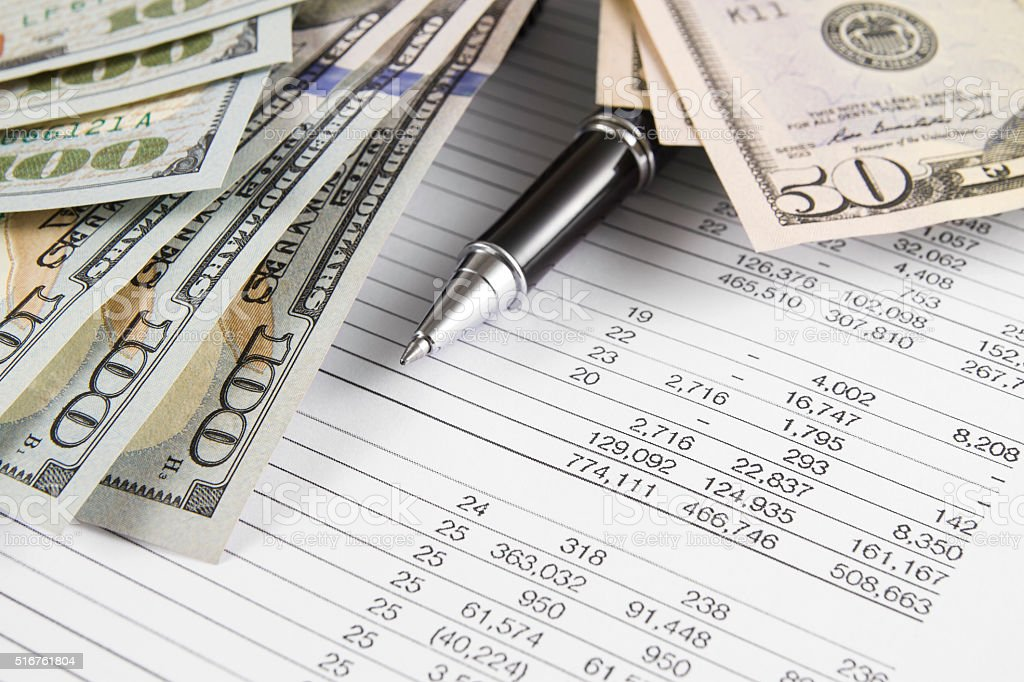 Financial Figures with Stack of Dollars stock photo