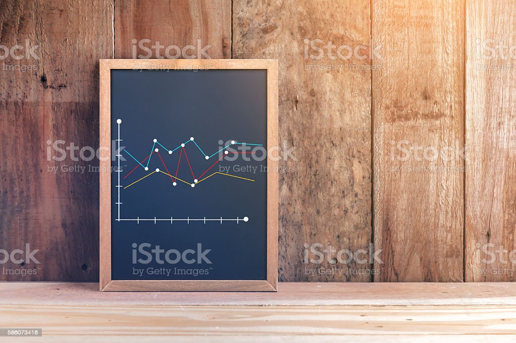 financial graph analysis on chalkboard texture background.jpg stock photo