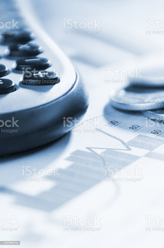 Financial graphs and charts with calculator and coins royalty-free stock photo