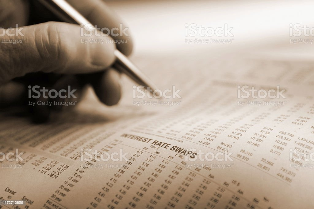 Financial news paper and a person holding a pen stock photo