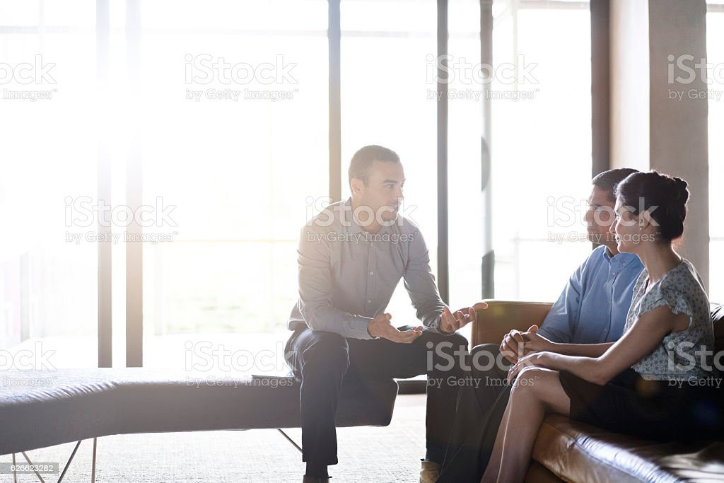 Financial planner talking with couple in office stock photo