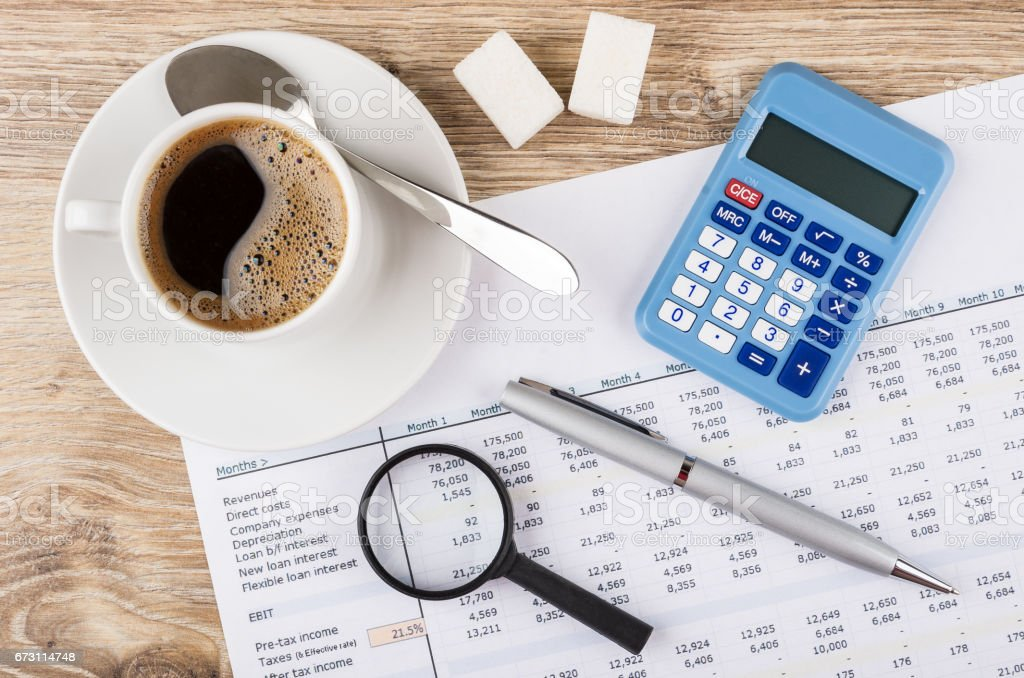 Financial printout, calculator, pen, magnifying glass and coffee on table stock photo