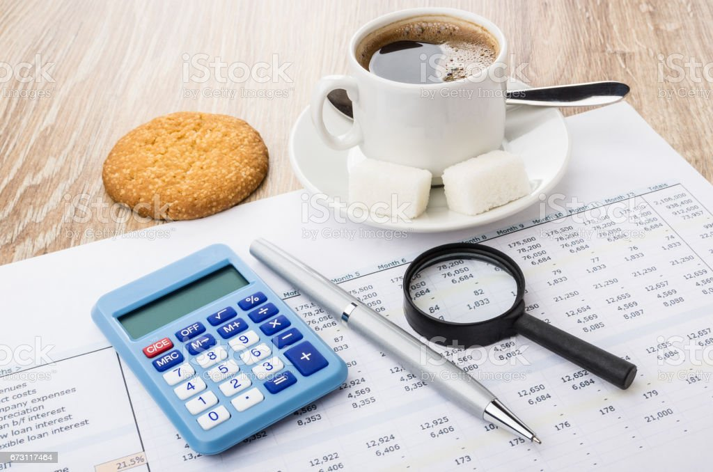Financial printout, calculator, pen, magnifying glass, coffee and cookies stock photo