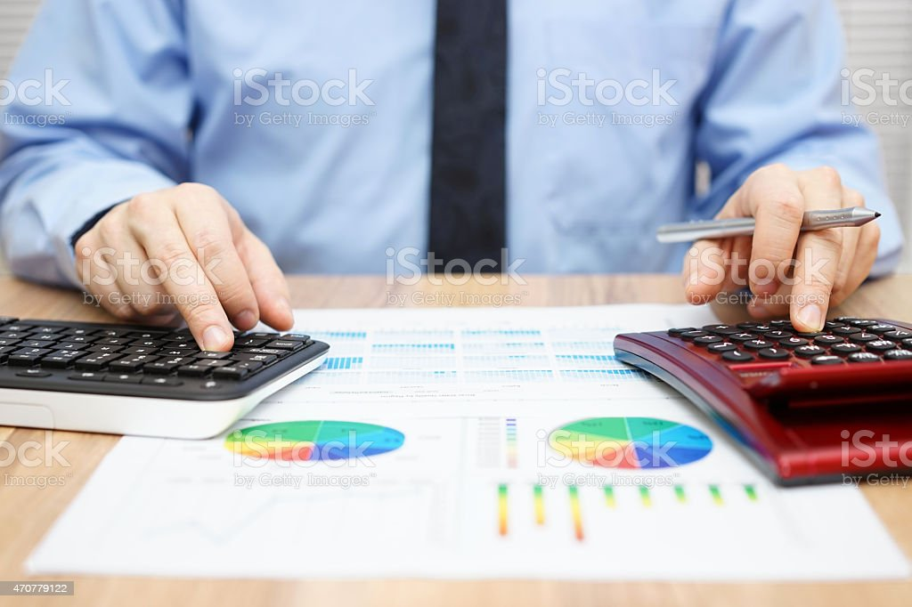 financial specialist is working with calculator and computer stock photo