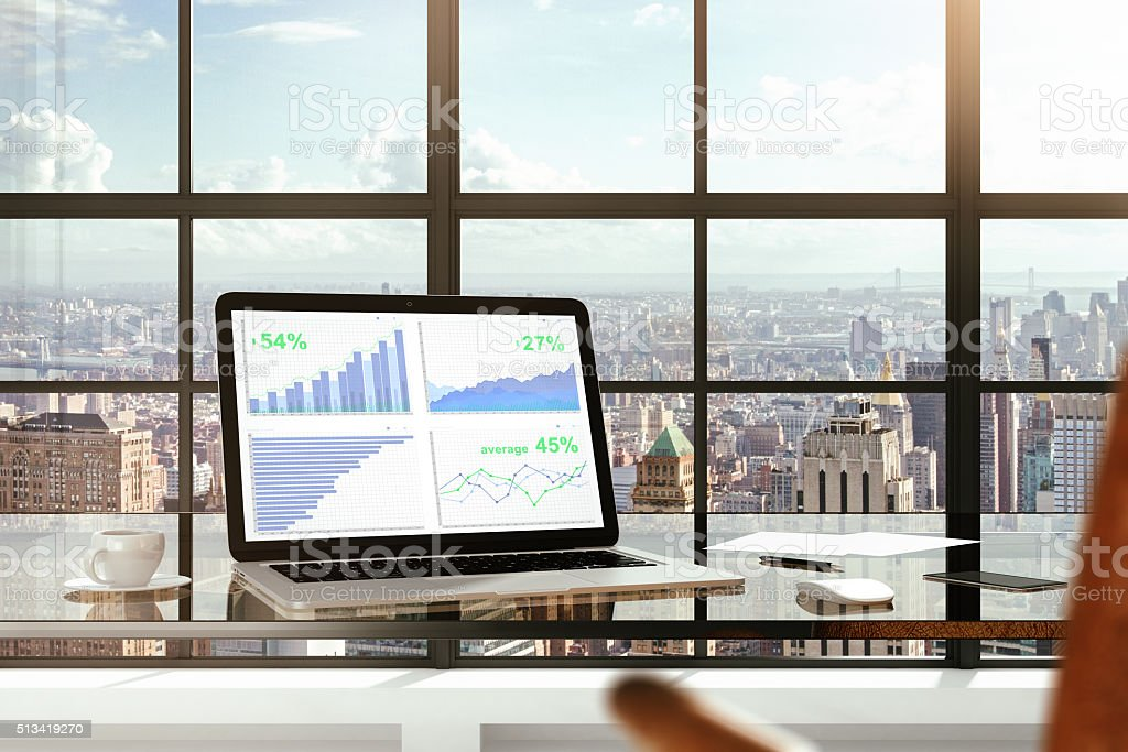 Financial statistics on laptop screen on glassy table in modern stock photo