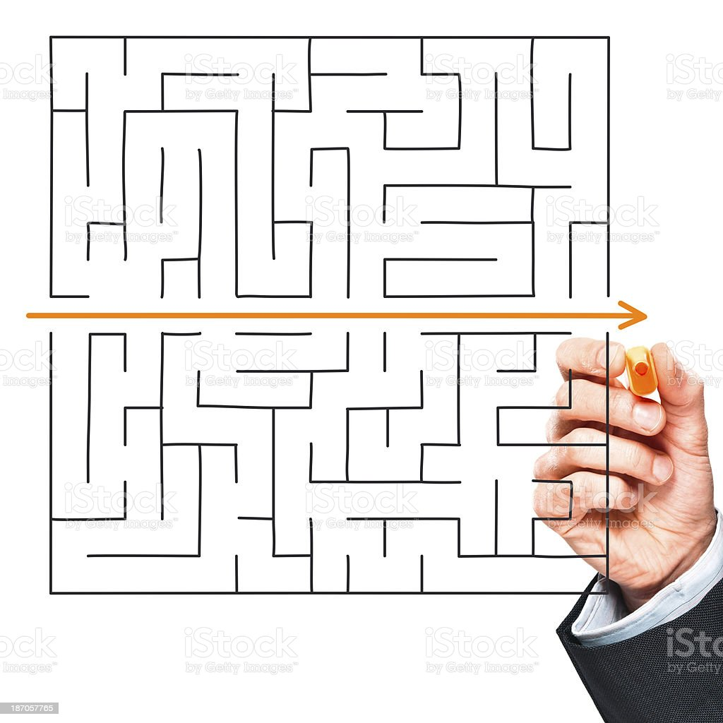 Find best solution. Businessman's hand drawing straight line through maze stock photo