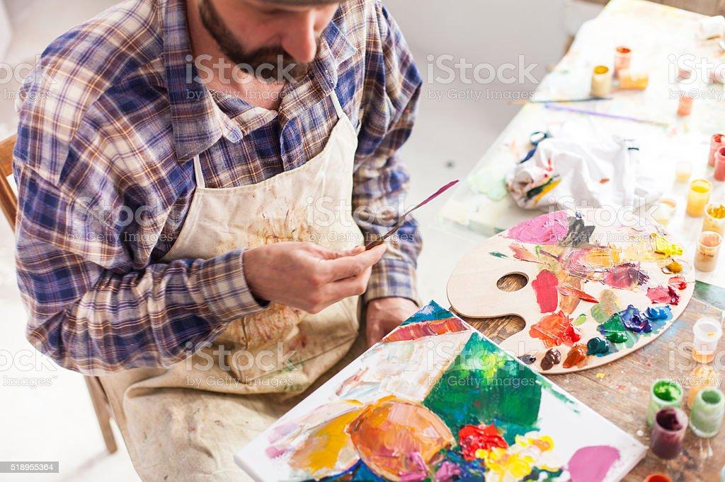 Fine art painter creating new artwork in his studio. stock photo