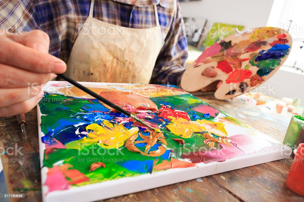 Fine art painter holding a palette and painting-close up stock photo