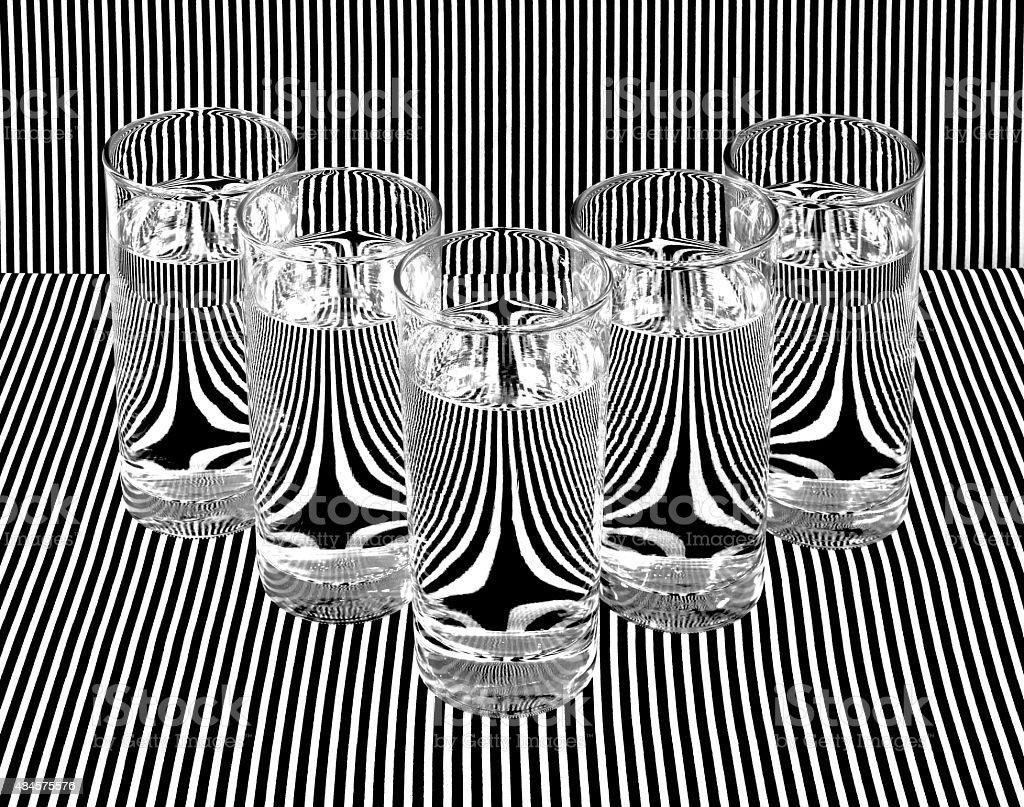 Fine Art Photograph Water Filled Glasses Refracting Black White Stripes stock photo