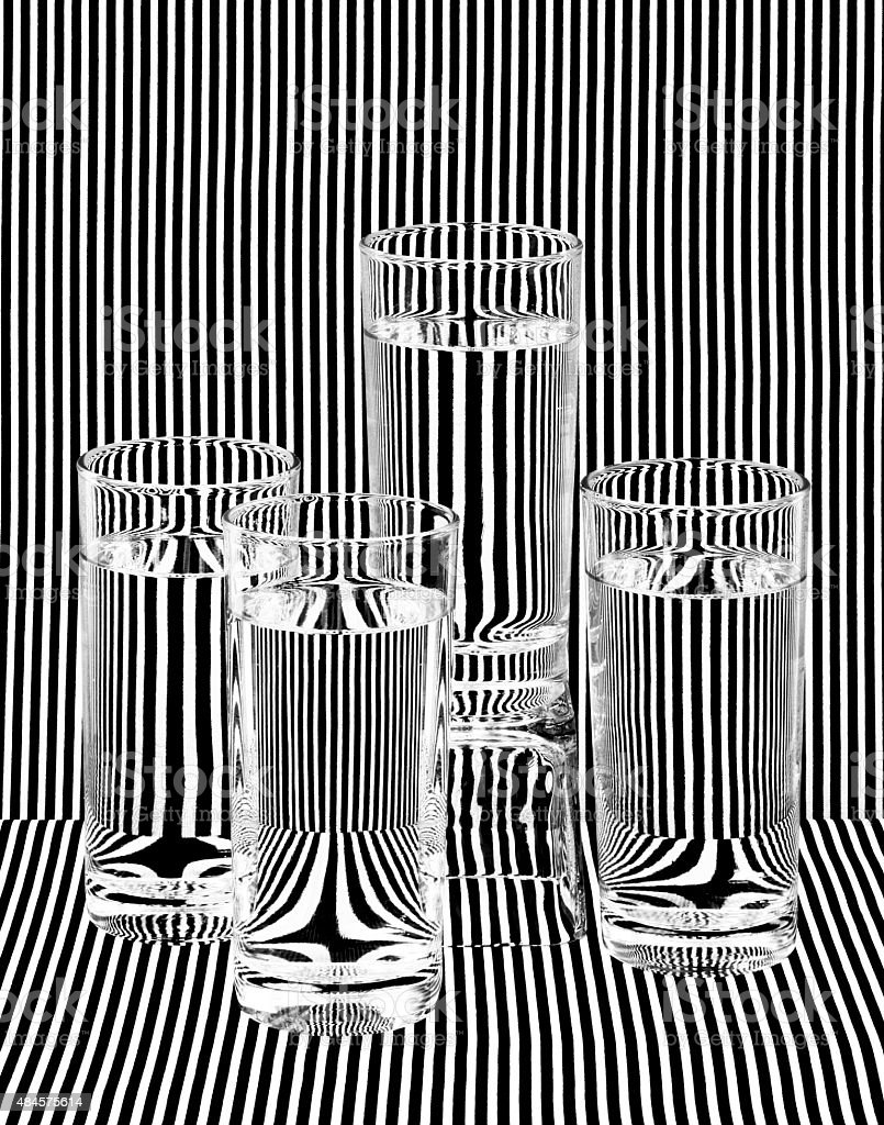 Fine Art Photograph Water Filled Glasses Refracting Black White Stripes stock photo