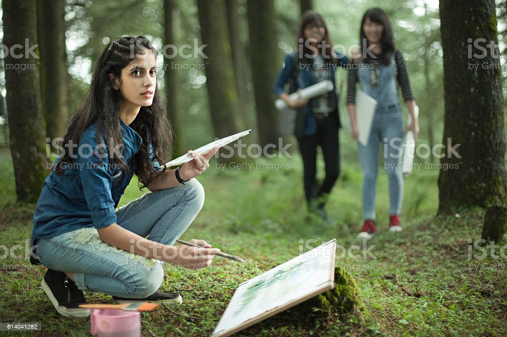 Fine art student making on location watercolor painting with friends. stock photo