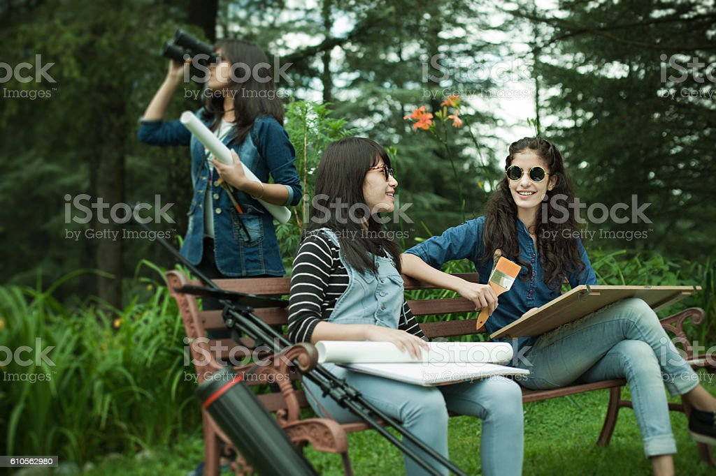 Fine Art students with drawing and painting equipments in park. stock photo