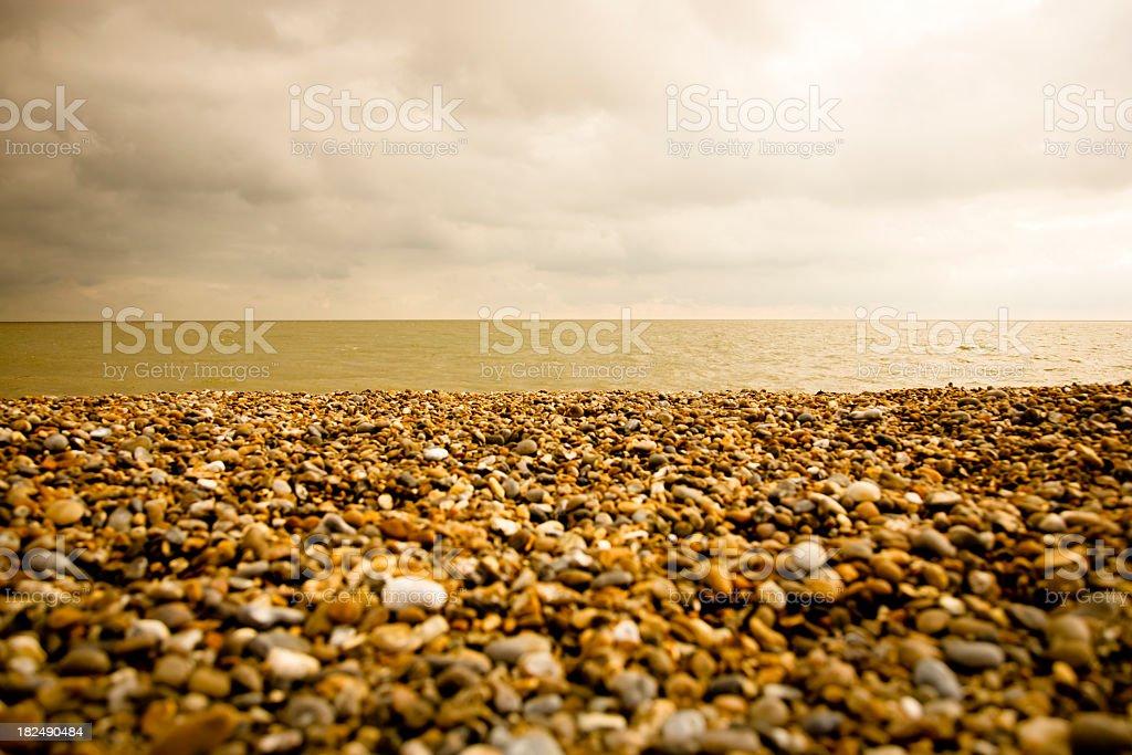 fine art style shingle beach with dramatic lit sky stock photo