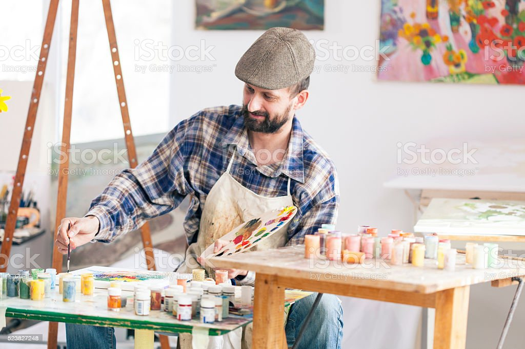 Fine artist painting at his workshop stock photo