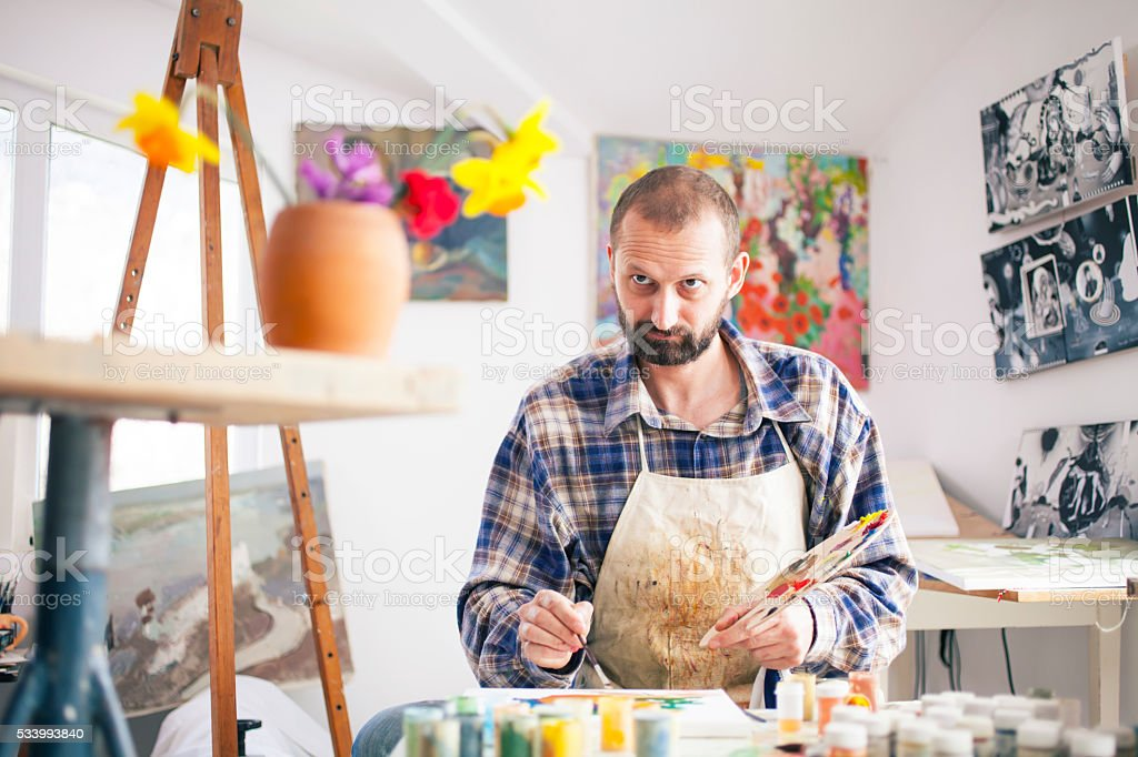 Fine artist painting at his workshop-looking at vase with flowers stock photo