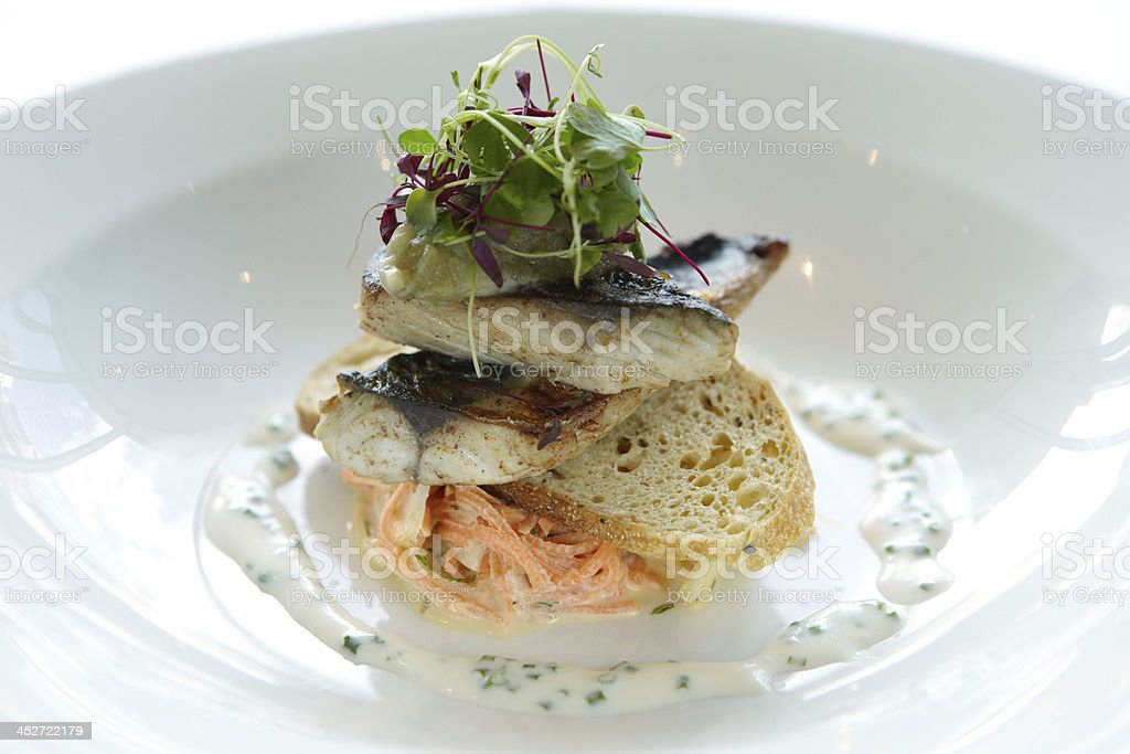 Fine dining Sea bass fillet starter with bread and coleslaw royalty-free stock photo