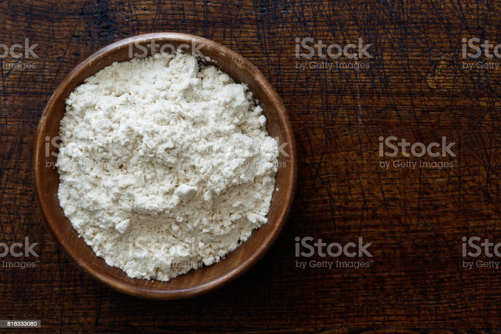 Fine white flour in dark wooden bowl isolated on dark brown wood from above. stock photo