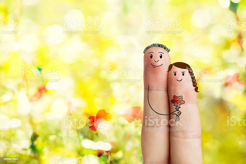 Finger art. Couple is embracing and holding red heart bouquet stock photo