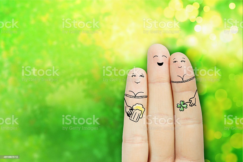 finger art. Man is embracing two girls and drinking beer stock photo