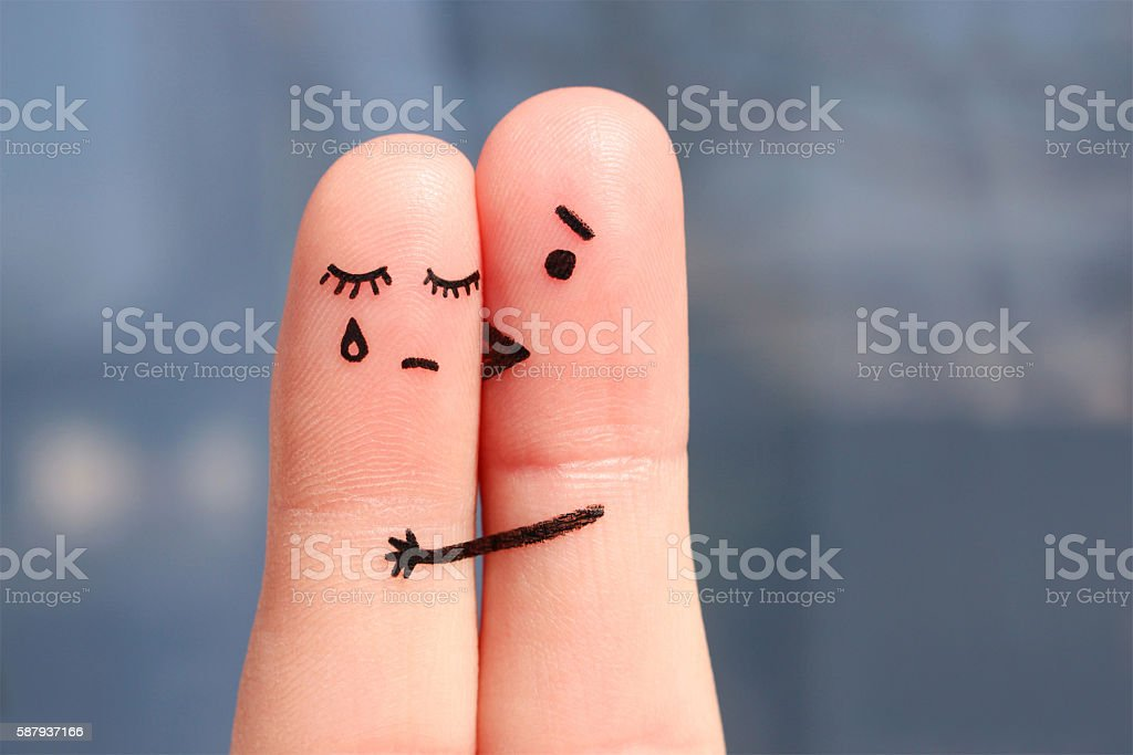 Finger art of displeased couple. Woman cries, man reassures her stock photo