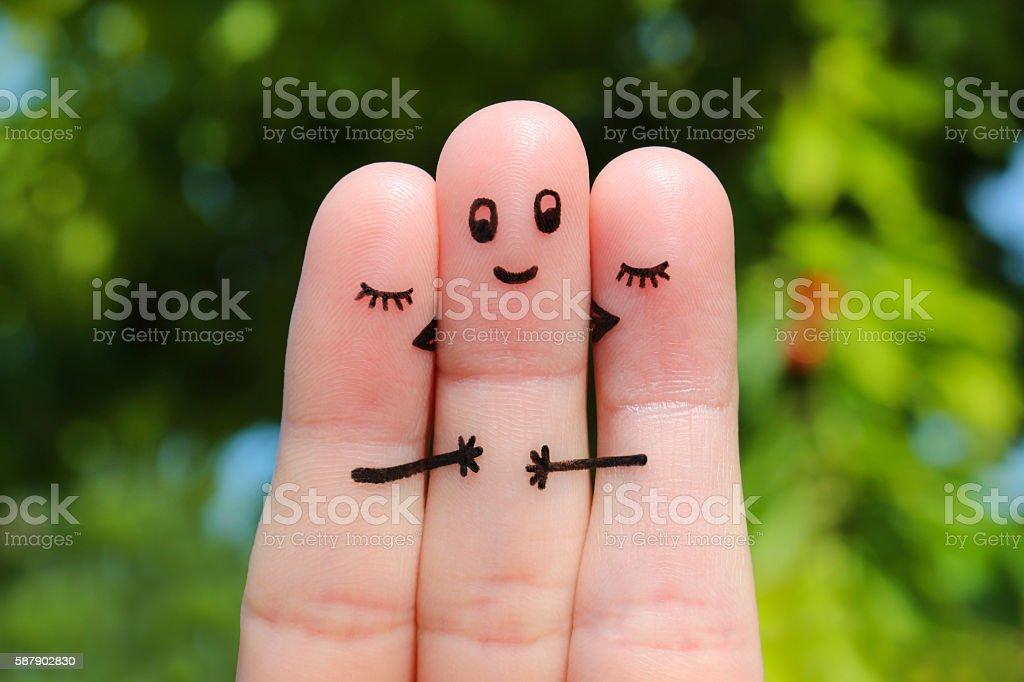 Finger art. Two women kissing a man. stock photo