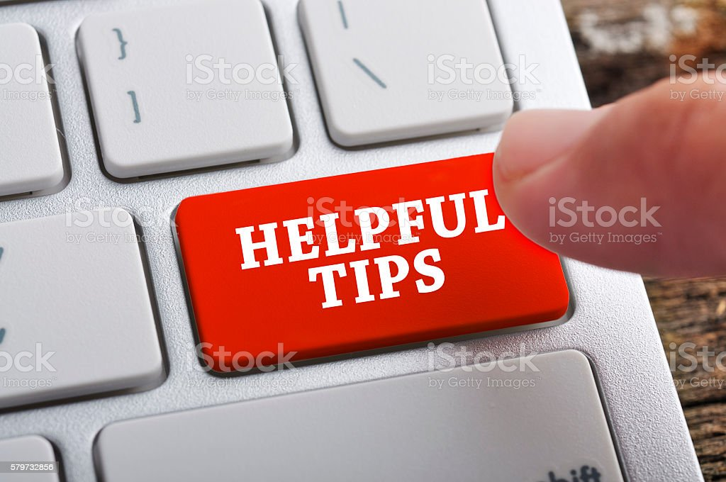 Finger at 'HELPFUL TIPS' On Keyboard Button stock photo
