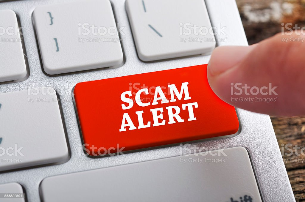 Finger at 'SCAM ALERT' On Keyboard Button stock photo