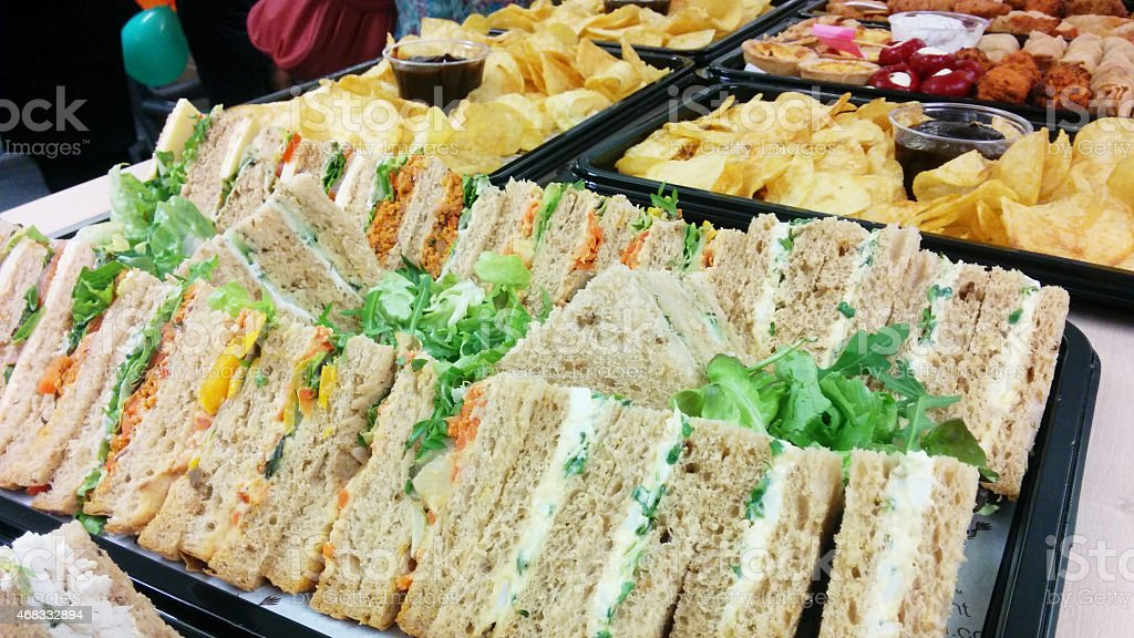 Finger foods such as sandwiches and chips on black trays stock photo