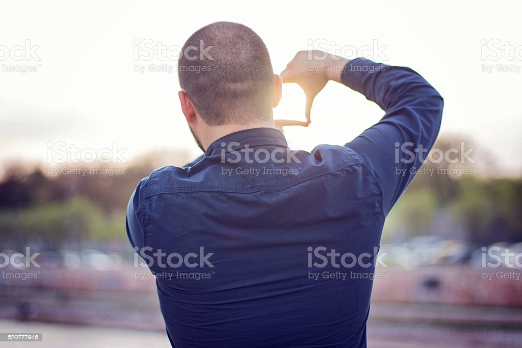 Finger frame. Young man framing landscape stock photo