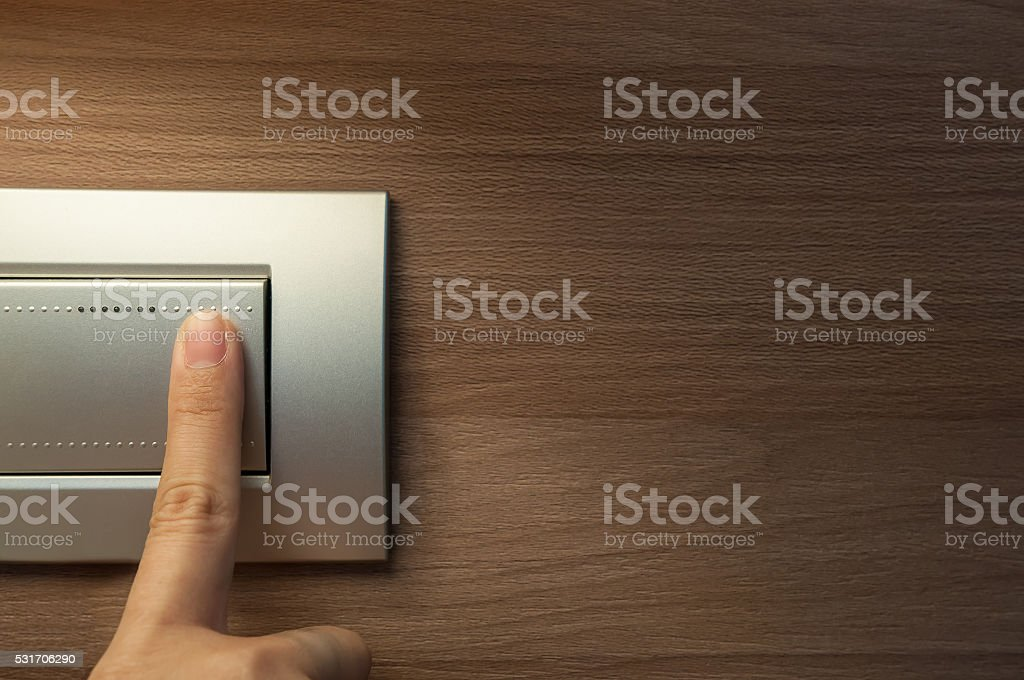 finger is turning on a grey light switch. stock photo