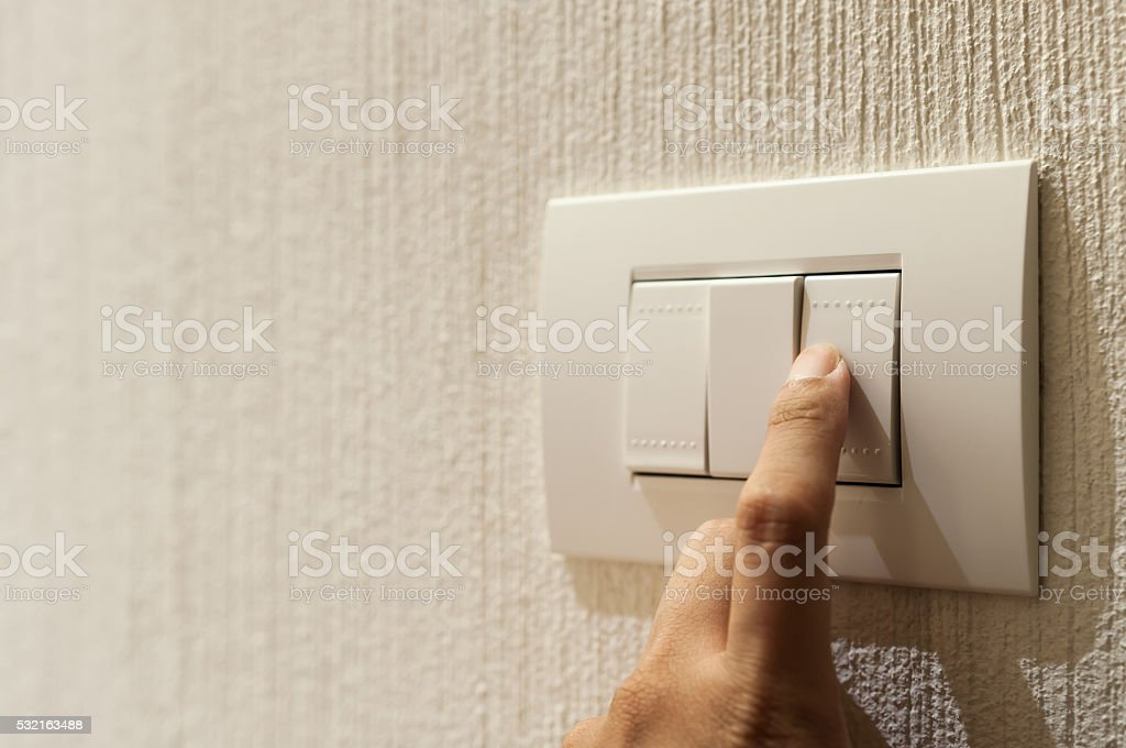finger is turning on a lighting switch stock photo