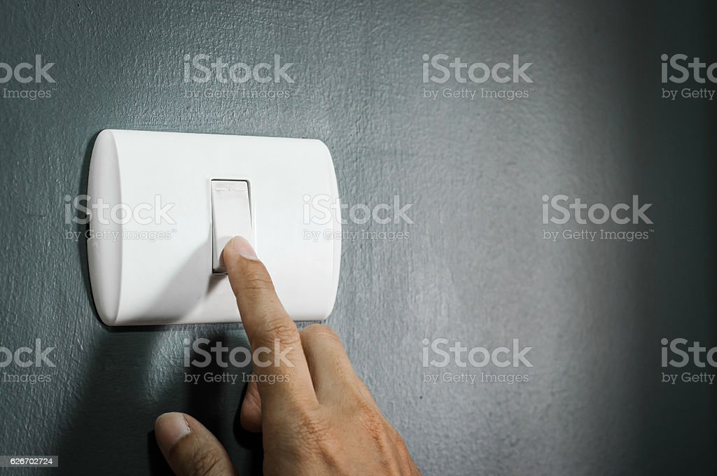 Finger is turning on rough dark wall. stock photo