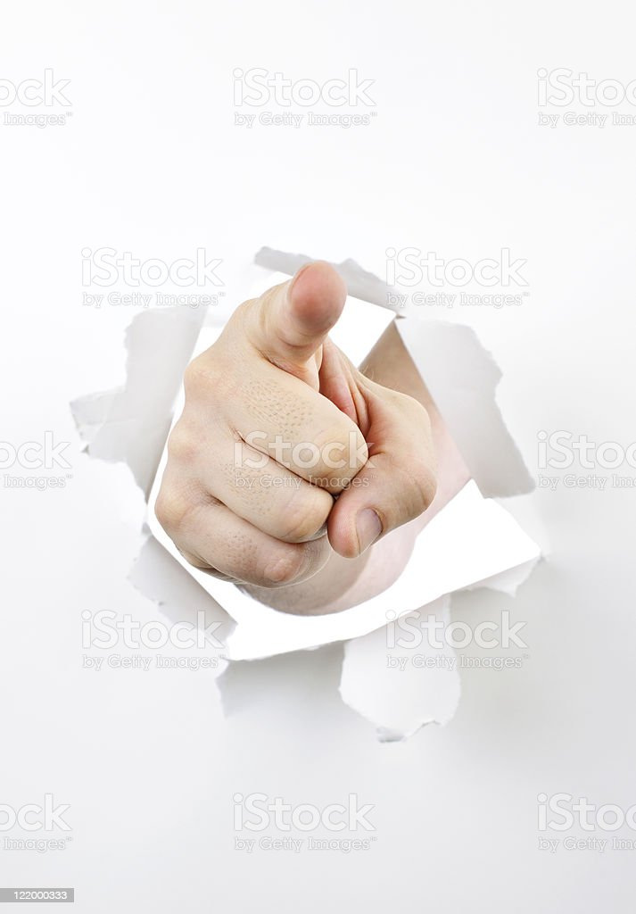 Finger pointing through hole in paper stock photo