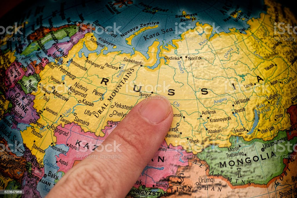 Finger pointing to Russia on a globe stock photo
