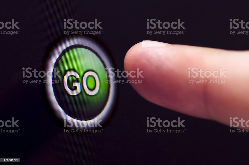 Finger presses green GO button on touchscreen royalty-free stock photo