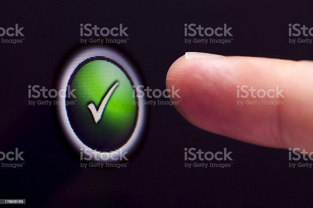 Finger presses green tick button on a touchscreen royalty-free stock photo