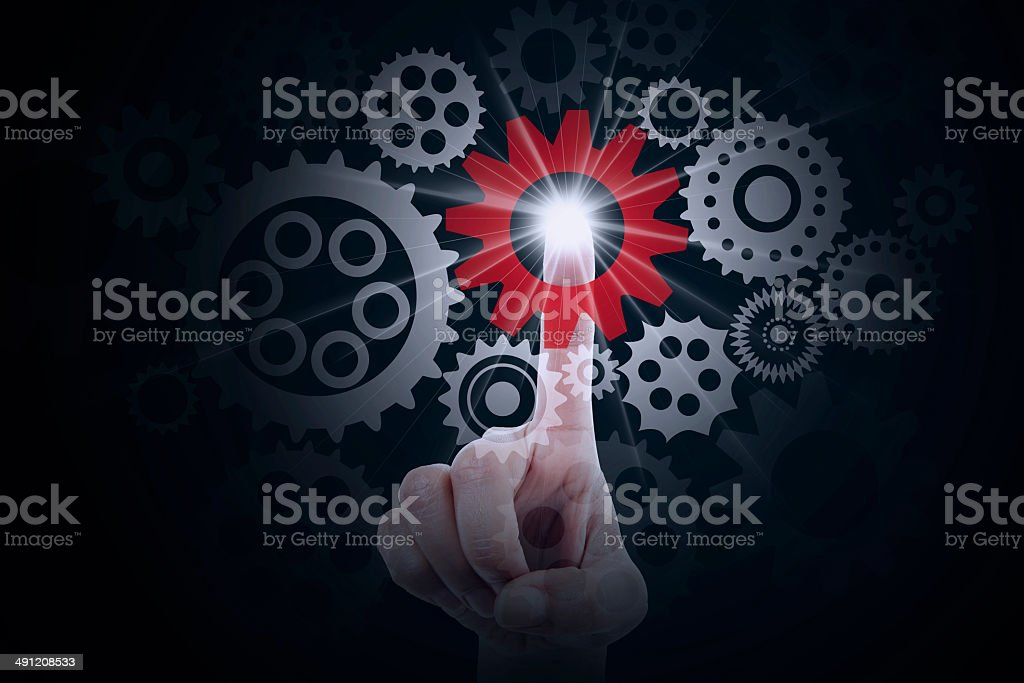 Finger pressing a cog gear royalty-free stock photo