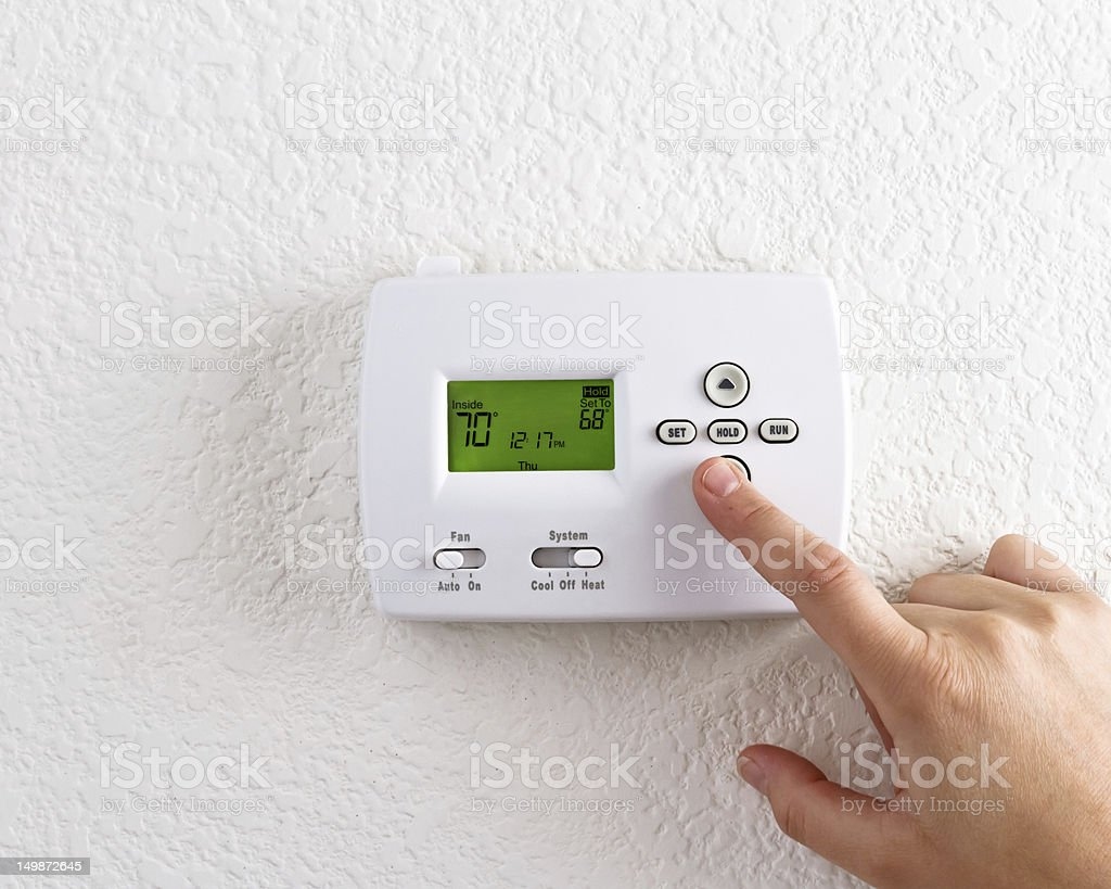 A finger pressing a digital thermostat stock photo