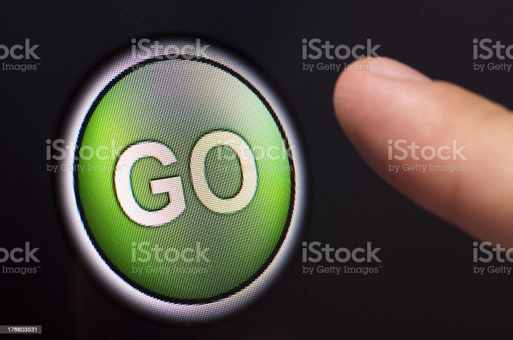 Finger pressing a green GO button on touchscreen royalty-free stock photo
