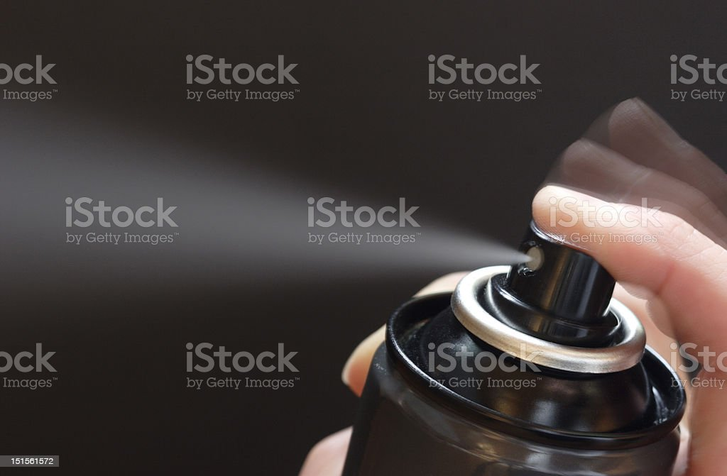 Finger pressing a spray can stock photo